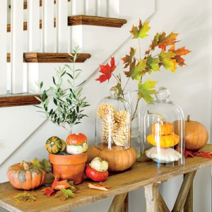 little pumpkins under cloches on an entryway table